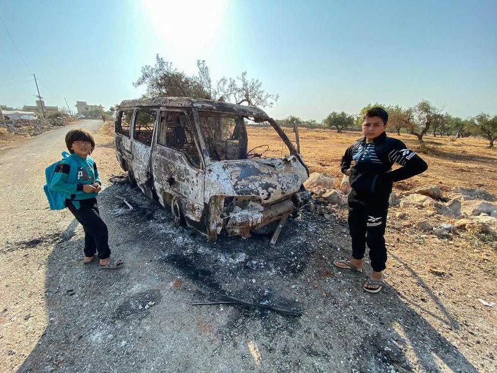 Niños sirios se paran junto a un vehículo quemado en la zona donde habría sido abatido el líder del Estado Islámico. (AFP / Omar HAJ KADOUR).