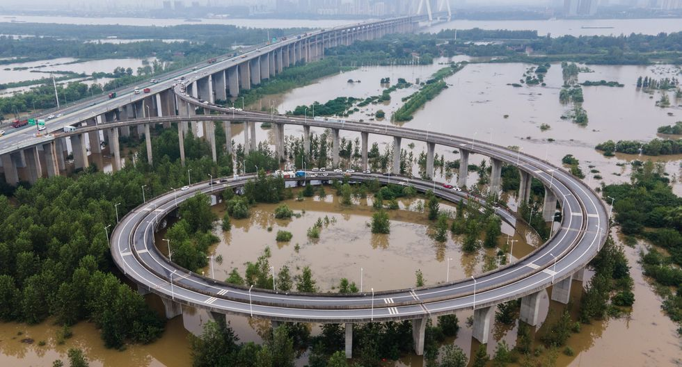 Esta vista aérea muestra un puente que conduce a la inundada isla de Tianxingzhou, que se convertirá en una zona de flujo de inundación para aliviar la presión del alto nivel de agua en el río Yangtze, en Wuhan. (Foto: STR / AFP)
