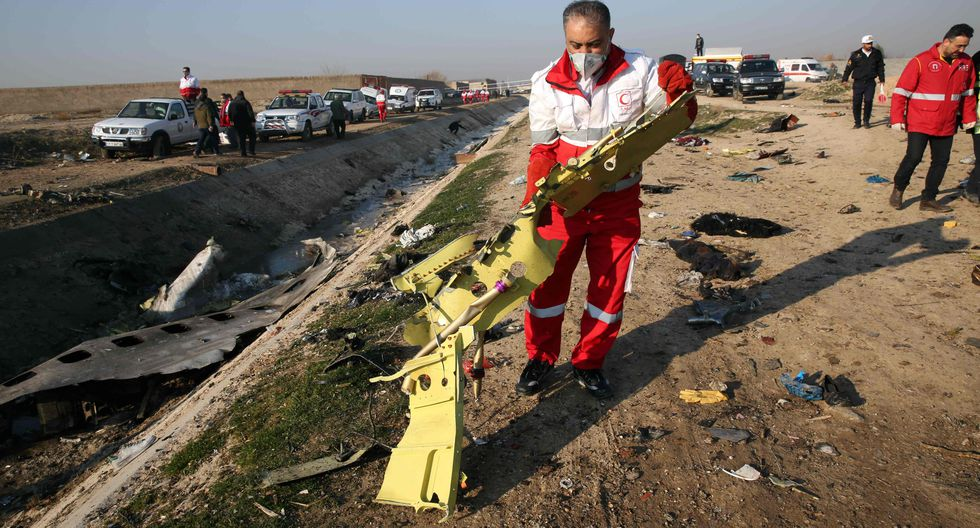 EDITORS NOTE: Graphic content / TOPSHOT - Rescue teams recover debris from a field after a Ukrainian plane carrying 176 passengers crashed near Imam Khomeini airport in the Iranian capital Tehran early in the morning on January 8, 2020, killing everyone on board. The Boeing 737 had left Tehran's international airport bound for Kiev, semi-official news agency ISNA said, adding that 10 ambulances were sent to the crash site. / AFP / -