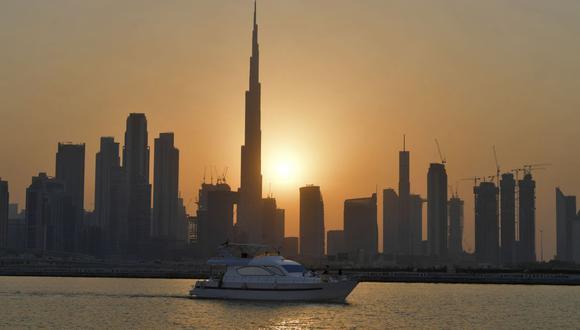 El sol se pone detrás de Burj Khalifa y otros edificios de gran altura, en la ciudad emiratí de Dubái, el 12 de septiembre de 2020. (Foto de Karim SAHIB / AFP).