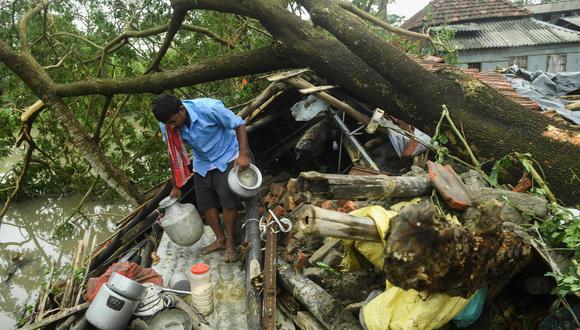 Un hombre salva objetos de su casa que fue destruida por el ciclón Amphan en Midnapore, Bengala Occidental (India). Foto: AFP / Dibyangshu SARKAR