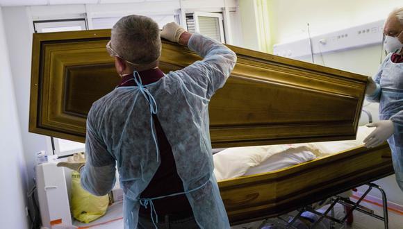 Empleados de la funeraria Lantz cierran el ataúd de una víctima de coronavirus en un hospital en Mulhouse, este de Francia. (AFP / SEBASTIEN BOZON).