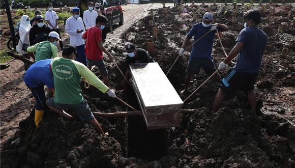 Trabajadores bajan un ataúd durante la inhumación de una víctima fatal de COVID-19, en una zona especial para esos cadáveres en el cementerio público de Jombang, el lunes 21 de junio de 2021 en Tangerang, en las afueras de Yakarta, Indonesia. (AP Foto/Tatan Syuflana).