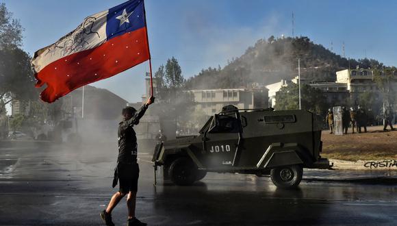 Un manifestante sostiene una bandera de Chile frente a un vehículo de la policía antidisturbios durante una protesta contra el gobierno del presidente Sebastián Piñera el 6 de noviembre de 2020. (MARTIN BERNETTI / AFP).