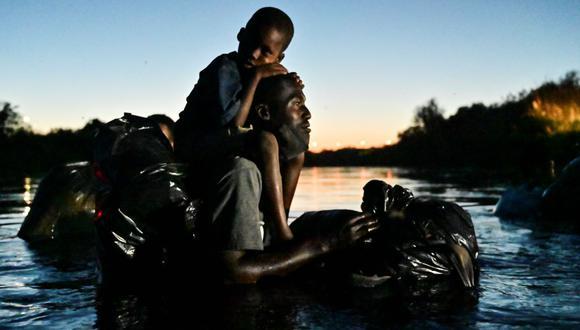 Un hombre carga a un niño sobre sus hombros mientras migrantes haitianos cruzan el río Grande entre Ciudad Acuña, estado de Coahuila, México, el 23 de septiembre de 2021. (PEDRO PARDO / AFP).