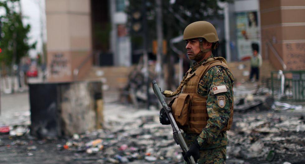 Un militar custodia el perímetro de un supermercado que fue saqueado en santiago de Chile. (Pablo VERA / AFP).