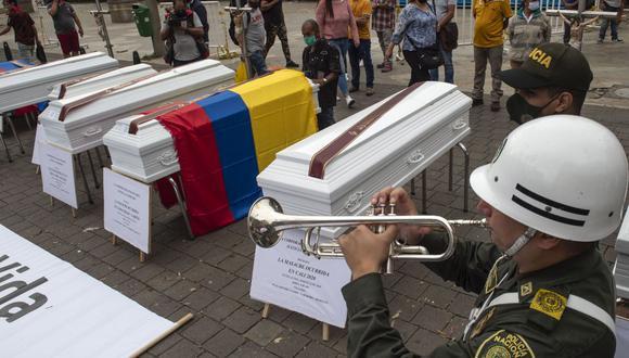 Un policía toca la trompeta junto a un conjunto de ataúdes colocados como parte de una protesta contra la violencia en Colombia, donde ocurrieron varias masacres en los últimos días. (Foto de JOAQUIN SARMIENTO / AFP).
