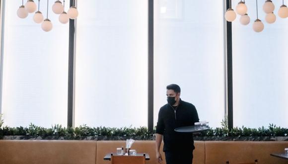 Imagen referencial. Un trabajador que usa una mascarilla protectora se preparapara abrir un restauranteen Nueva York, Estados Unidos, 30 de septiembre.