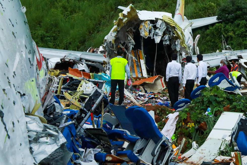 Personas inspeccionan los restos de un avión de Air India Express en el estado de Kerala en India. (AFP / Arunchandra BOSE).