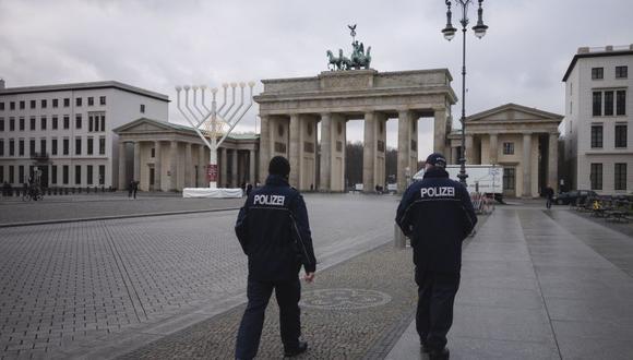 Alemania inició un cierre más duro en un esfuerzo por reducir el alto número de casos de coronavirus COVID-19. En la imagen, oficiales de policía patrullan en un desierto de la Pariser Platz frente a la Puerta de Brandenburgo en Berlín. (Foto: AP / Markus Schreiber)
