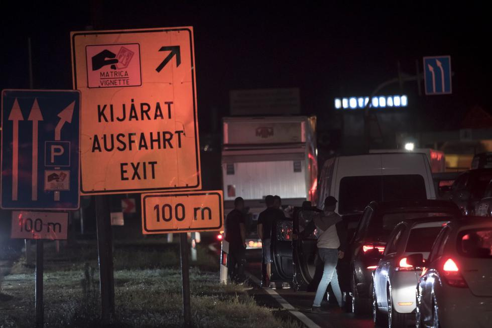 La gente se para junto a sus carros mientras hacen una fila para cruzar la frontera entre Austria y Hungría. (EFE / EPA / CHRISTIAN BRUNA).