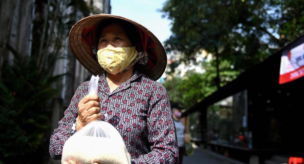 Una mujer que usa mascarilla lleva una bolsa de arroz en Hanoi, Vietnam, país que ha enfrentado de manera exitosa el coronavirus. (AFP / Nhac NGUYEN).