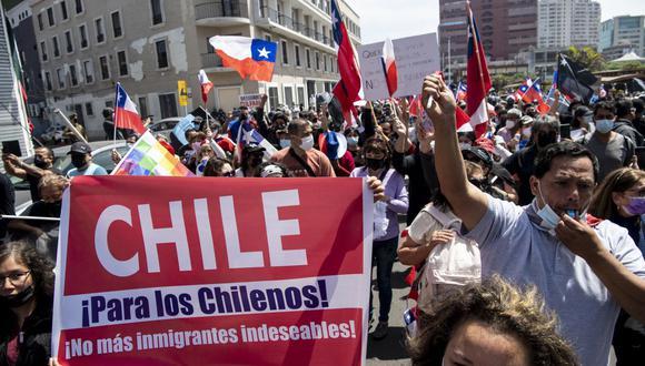 Personas protestan con fuertes carteles contra la masiva migración venezolana que ha llegado a Chile. (Foto: de Martin Bernetti / AFP)