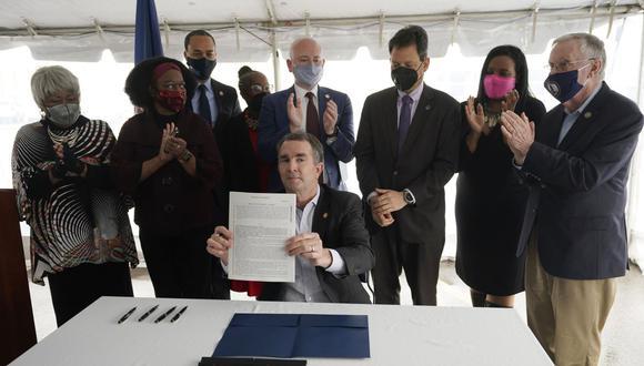 El gobernador de Virginia Ralph Northam, sentado en el centro, muestra un proyecto de ley firmado que abolió la pena de muerte mientras está rodeado de legisladores y activistas en el Centro Correccional de Greensville en Jarratt, el miércoles 24 de marzo de 2021. (AP/Steve Helber).