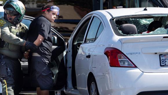 Una mujer no identificada es detenida después de que testigos dijeron que condujo su automóvil contra una multitud de manifestantes en Yorba Linda, California. (Foto: AP/Mindy Schauer/The Orange County Register).