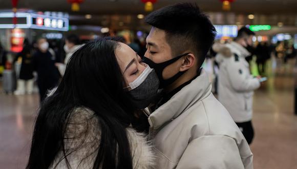 Una pareja, provista de mascarillas, se dan un beso de despedida en la estación de tren de Beijing, China, en enero de este año. (Photo by NICOLAS ASFOURI / AFP)