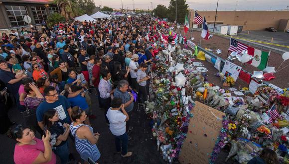 La gente reza y presenta sus respetos en el improvisado monumento a las víctimas del tiroteo que dejó un total de 22 personas muertas en el Cielo Vista Mall WalMart (fondo) en El Paso, Texas, el 6 de agosto de 2019. (Foto: AFP / Mark RALSTON).