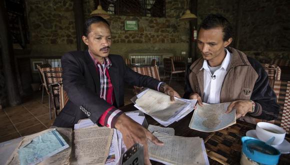Steven Lacchin, de 39 años, a la izquierda, se reúne por primera vez con Gerald Erebon, de 30 años, a la derecha, a quien las pruebas de ADN indican que es su medio hermano, y le muestra documentos relacionados con el misionero italiano. (Foto: Archivo/AP).