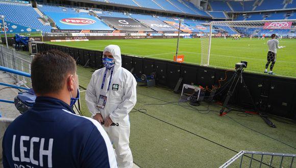 Hombre con traje de protección afuera de un campo de fútbol de Polonia, antes del primer partido a disputarse en medio de la pandemia del Covid-19. Foto: AFP.