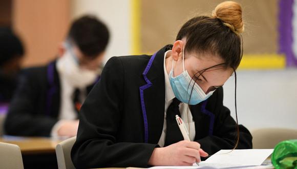 Los estudiantes participan en una clase en Park Lane Academy en Halifax, noroeste de Inglaterra, el 17 de marzo de 2021, en plena pandemia de coronavirus. (Foto de Oli SCARFF / AFP).