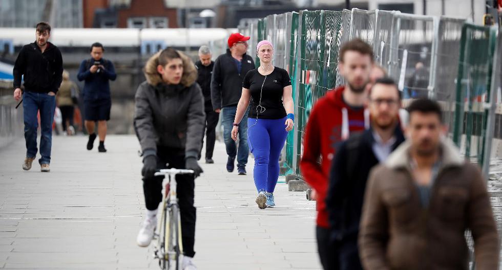 Un grupo de peatones cruzan el Puente de Londres en el centro de la ciudad. La gente comienza a regresar al trabajo después de que se redujeron las restricciones por la pandemia de COVID-19. (Tolga AKMEN / AFP)