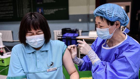 Una estudiante reacciona cuando recibe la vacuna Sinopharm contra el coronavirus covid-19 en una escuela secundaria en Shenyang, en la provincia de Liaoning, en el noreste de China. (Foto: AFP).