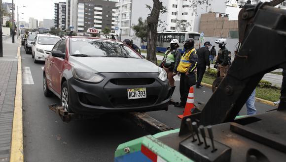 Colectivo de placa ACH-393 es llevado por la grúa de la municipalidad de Miraflores al depósito de la ATU en Ate. (Foto: César Campos)