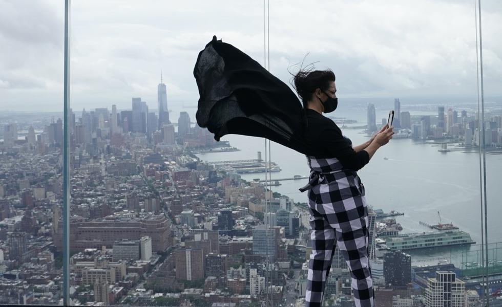 Anissa Barbato de Nueva York mira a la ciudad mientras toma fotos desde The Edge (el borde), la azotea abierta más alta en el hemisferio occidental. (Foto: AFP)