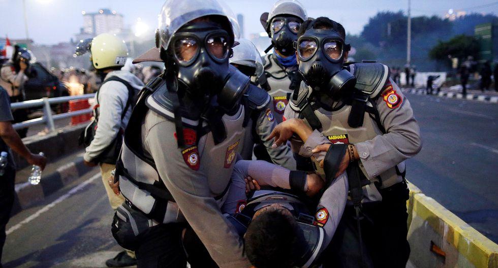 Los agentes de la policía antidisturbios de Indonesia llevan a un colega herido durante un enfrentamiento con estudiantes fuera del edificio del Parlamento en Yakarta. (EFE / EPA / MAST IRHAM).
