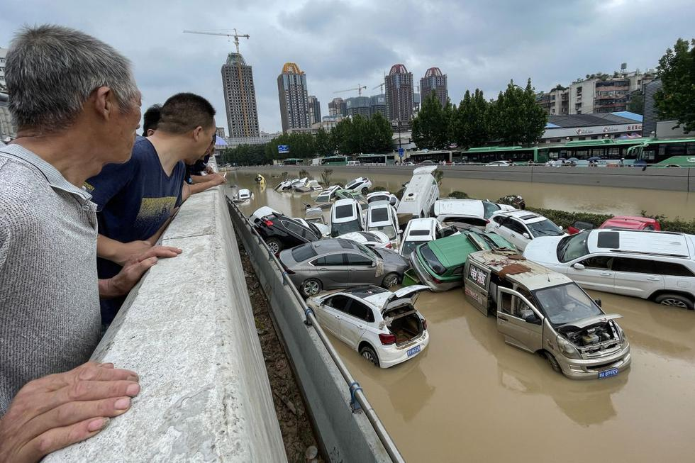 People see cars washed away by floods following heavy rains in Zhengzhou.  (Photo STR / AFP).