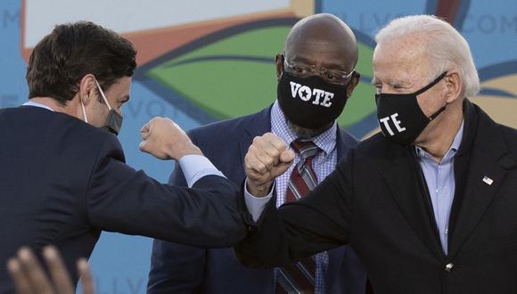 Los candidatos demócratas al Senado Jon Ossoff (izquierda), Raphael Warnock (centro) y el presidente electo de Estados Unidos Joe Biden chocan los codos en el escenario durante un mitin en Georgia. (Foto de JIM WATSON / AFP).