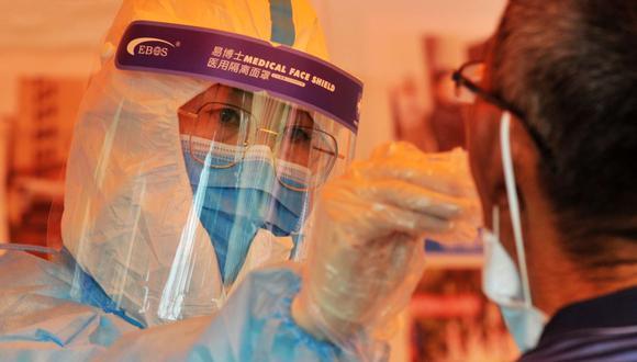 Personal sanitario realiza una prueba de ácido nucleico a un residente luego de que se detectara un nuevo brote del coronavirus COVID-19 en Qingdao. (Foto: AFP).