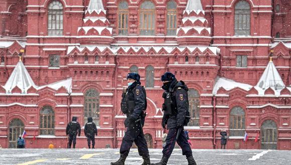 Dos policías con una máscara facial para protegerse contra la enfermedad del coronavirus covid-19 caminan por la Plaza Roja bajo la nieve cerca del Kremlin en Moscú el 8 de marzo de 2021. (Foto referencial, Yuri KADOBNOV / AFP).