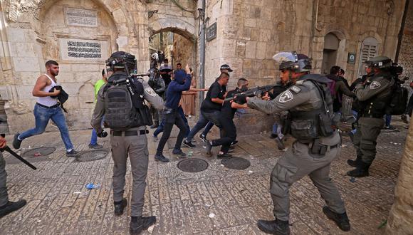 Los manifestantes palestinos huyen de las fuerzas de seguridad israelíes en medio de enfrentamientos en la Ciudad Vieja de Jerusalén. (Foto de EMMANUEL DUNAND / AFP).