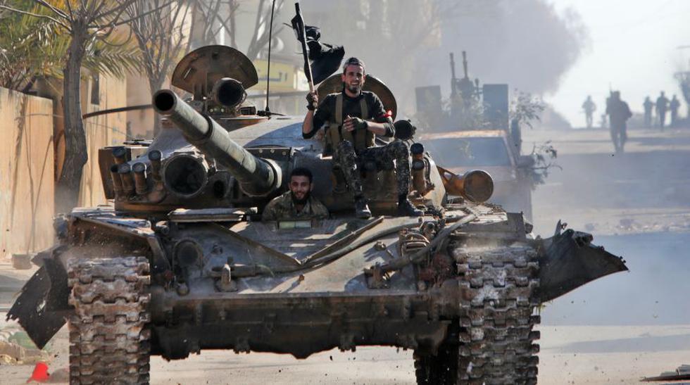 Combatientes sirios respaldados por Turquía viajan en un tanque en la ciudad de Saraqib. Las grandes pérdidas se producen después de semanas de crecientes tensiones entre Turquía y Rusia, un firme aliado de Siria. (AFP).