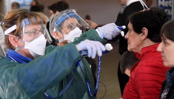 Personal sanitario que usa trajes protectores contra el coronavirus toma la temperatura de las personas que están en el hospital Maugeri, en Pavia, en el norte de Italia. (EFE / EPA / Daniel Dal Zennaro).