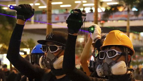 Los manifestantes de Hong Kong usan rayos láser para evitar ser registrados por las cámaras de reconocimiento facial de la policía. (AP).