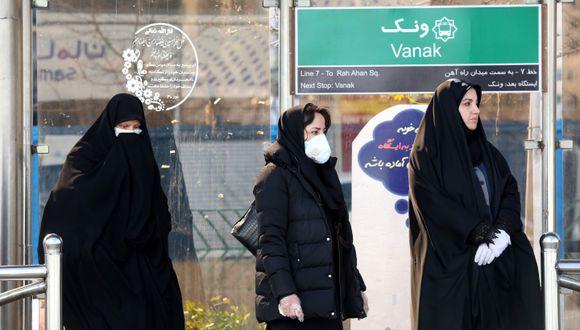 Un grupo de mujeres que lleva máscaras protectoras contra el coronavirus espera el bus en una estación de Teherán, la capital de Irán. (AFP / ATTA KENARE).