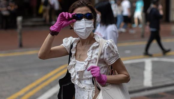 Una mujer que usa una máscara facial y guantes cruza una intersección en Hong Kong, China, el 27 de julio de 2020. A partir del 29 de julio a la medianoche y durante siete días, Hong Kong implementará medidas de distanciamiento social más estrictas para reducir la tercera ola de contagios de coronavirus. (EFE / EPA / JEROME FAVRE).