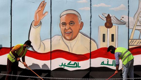Trabajadores municipales iraquíes barren una calle frente a un dibujo gigante del papa Francisco en la pared de la iglesia católica Sayidat al-Nejat (Nuestra Señora de la Liberación), en la capital de Irak, Bagdad, el 26 de febrero de 2021. (Foto de AHMAD AL-RUBAYE / AFP).
