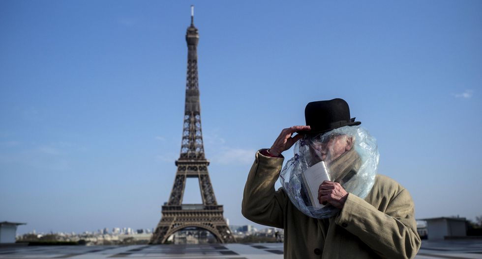 Un hombre usa una bolsa de plástico para protegerse del coronavirus cerca de la Torre Eiffel en París (Francia). (EFE/EPA/Julien de Rosa).