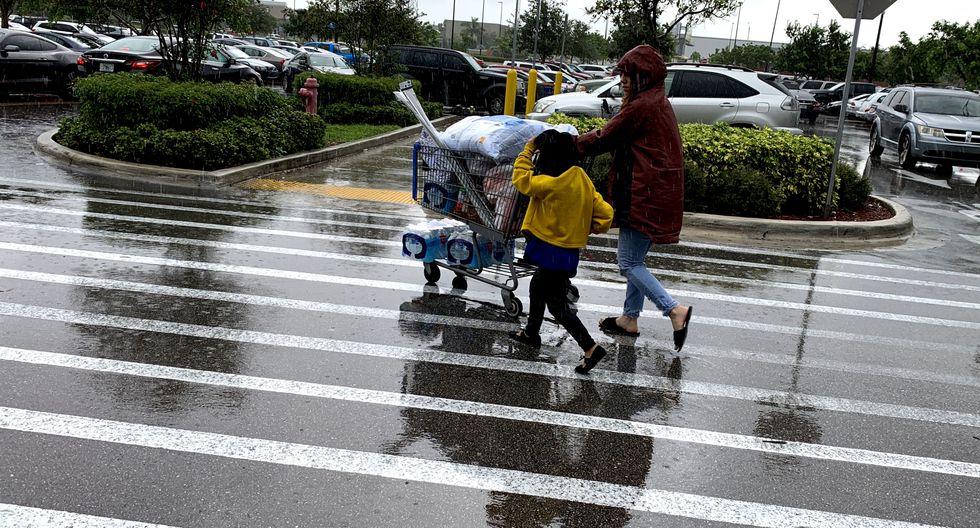 Una mujer y un niño tiran de un carrito con víveres afuera de Walmart durante una ráfaga de viento del huracán Dorian. (Foto: AFP)
