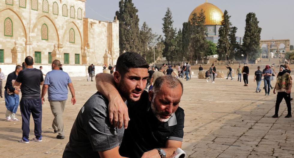 Un palestino ayuda a otro manifestante herido en medio de enfrentamientos con las fuerzas de seguridad israelíes en el complejo de la mezquita Al-Aqsa de Jerusalén. (Foto de ahmad gharabli / AFP).