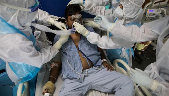 Los médicos y enfermeras que usan trajes de Equipo de Protección Personal atienden a un paciente con coronavirus COVID-19 en la Unidad de Cuidados Intensivos del Hospital Sharda, en Greater Noida, India. (Foto: XAVIER GALIANA / AFP).