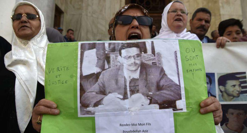 Una mujer argelina lleva el retrato de un hombre desaparecido mientras se manifiesta para exigir un cambio radical en todo el sistema político del país. (Foto: AFP)