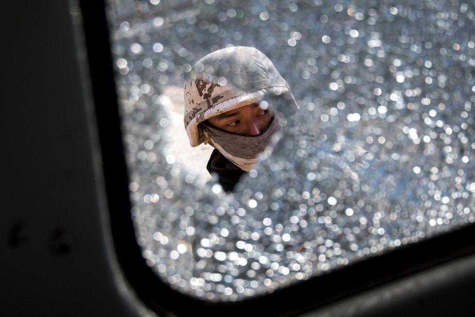 Un agente del Ejercito mexicano observa los orificios provocados por impactos de bala en un vehículo en la población de Villa Unión. (EFE/Miguel Sierra).