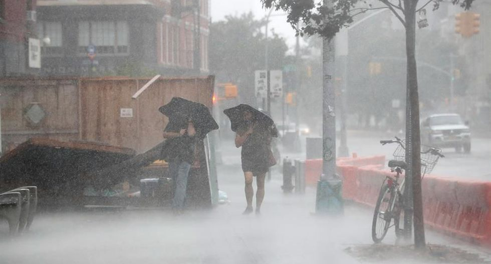 Dos personas caminan bajo el fuerte viento y la lluvia durante la tormenta tropical Isaías en Nueva York. (EFE / EPA / JASON SZENES).