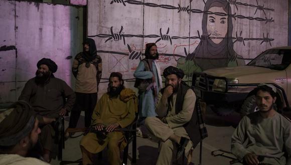 Miembros talibanes sentados frente a un mural que representa a una mujer detrás de un alambre de púas en Kabul, Afganistán, el martes 21 de septiembre de 2021. (AP Foto/Felipe Dana).