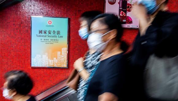 Un anuncio del gobierno (a la izquierda) que promueve la ley de seguridad nacional planificada por China se muestra dentro de una estación de trenes MTR en Hong Kong. (ISAAC LAWRENCE / AFP)