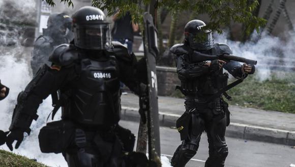 Miembros del Escuadrón Móvil Antidisturbios (ESMAD) disparan gases lacrimógenos durante una protesta de estudiantes en Medellín, Colombia. (Foto: JOAQUIN SARMIENTO / AFP).